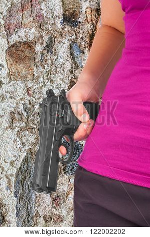 Woman holding gun in hand against a stone wall
