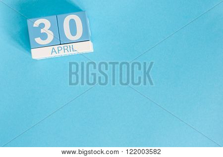April 30th. Image of april 30 wooden color calendar on blue background.  End month. Spring day, empt