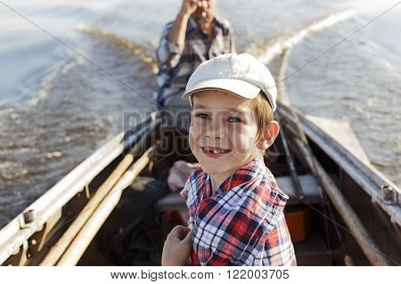 happy boy riding in a boat with his grandfather. child cheerfully smiling a toothless smile while sitting in a motorboat. the concept of connection between generations. return of grandfather and grandson with fishing