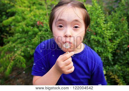 Little girl blowing dandelion in the park