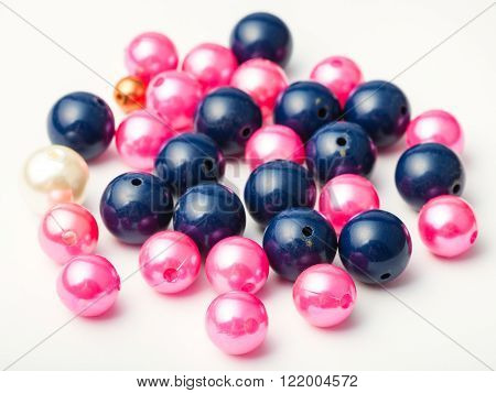 many blue and pink glass and plastic beads on white