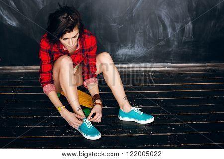 Woman Tying Shoe Laces. Ready For Skateboarding