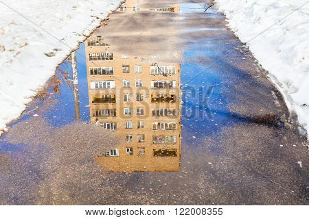 Reflection Of House In Puddle Of Melting Snow