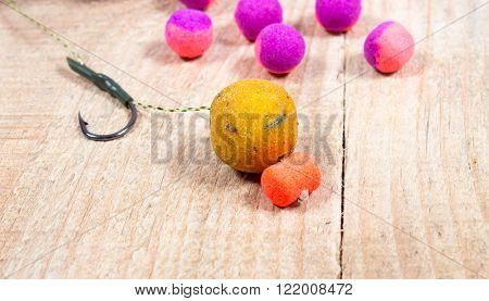 Carp Hook Boilies on wooden background. close up.