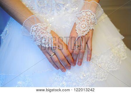 bride's hands in fishnet gloves on wedding dress background.