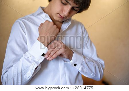groom wears cuff links on white shirt.