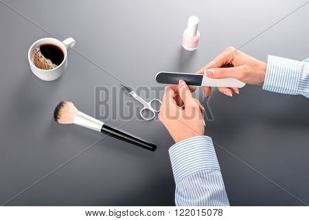 Close-up of woman making manicure. Close-up of female fixing nails. Small break at work. Invest some time into beauty.