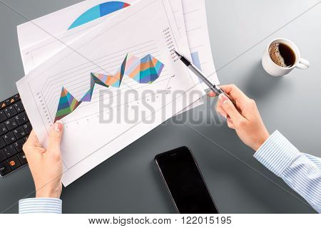 Lady with pen and charts. Woman holding charts and pen. Must study these reports. I see huge progress.