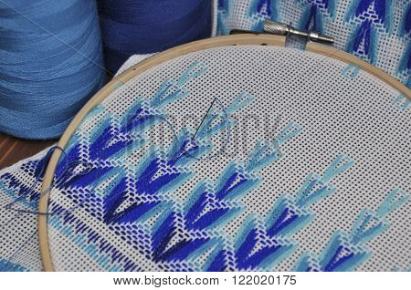 Detail of embroidery products with blue thread in wooden hoop