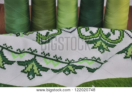 Traditional Ukrainian embroidered towel bright green thread in the hoop on the background of a wooden table