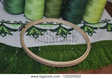 cross-stitch embroidery frame wooden towel in bright green thread
