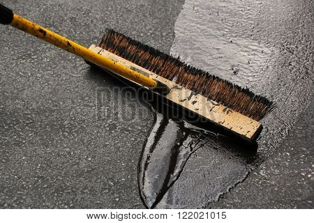 Sealing a damaged asphalt blcktop drive way with large brush