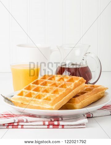 Stack of fresh made waffles with coffee and juice.