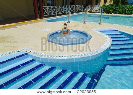 Cayo Coco island, Cuba, Sep 2, 2015  beautiful happy joyful little girl enjoying her leisure time and relaxing in outdoor small Jacuzzi near the pool at outdoor spa on sunny day