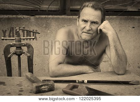 An elderly man thinking sitting on the bench at the table.On the table are locksmith tools