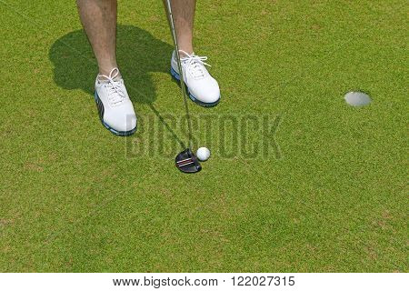 Afternoon view of a Golf player with white shoes holding a club with golf ball near a hole