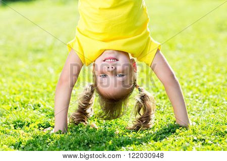 kid girl standing upside down on her head on grass in summer