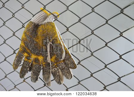 dirty gloves and wire mesh soft focus on gloves