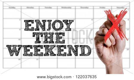 Hand writing the text: Enjoy The Weekend