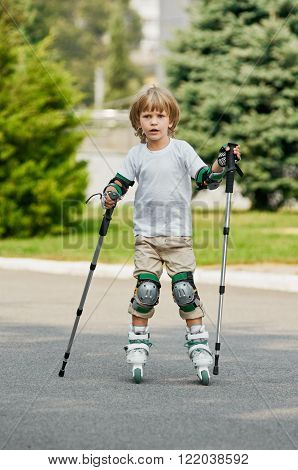 young boy on roller skates outdoors.  beginner. with nordic walking poles