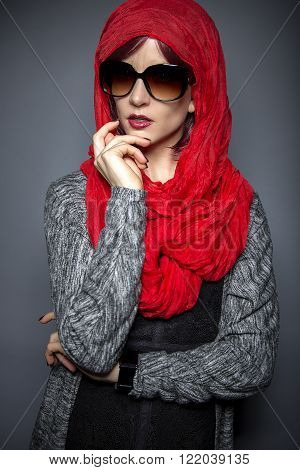 Woman wearing a Hijab head scarf.  This style is a combination of conservative religious styles and modern fashion.