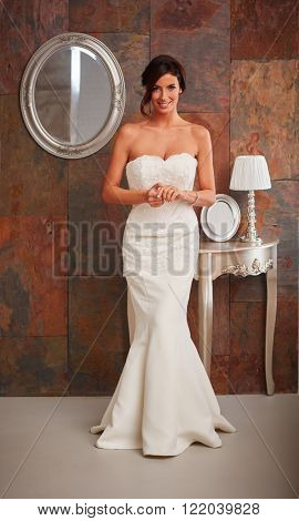 Beautiful bride standing in wedding gown, smiling happy. Full size.