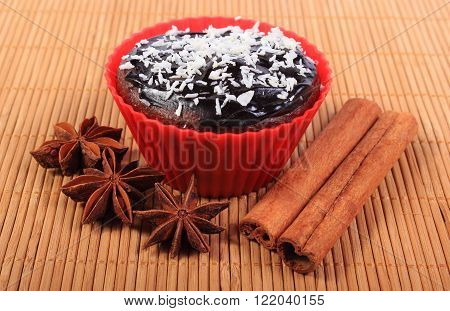 Homemade delicious fresh baked chocolate muffins with desiccated coconut in red silicone cups star anise and stick of cinnamon