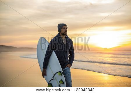 A surfer with his surfboard walking in the beach at the sunset