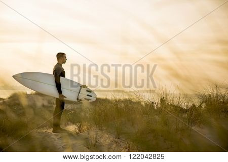 A surfer with his surfboard at the dunes looking to the waves