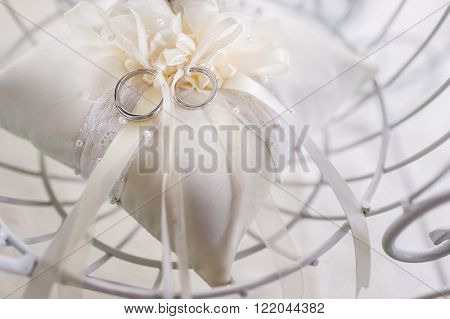 Beautiful wedding bands tied together on ring pillow.