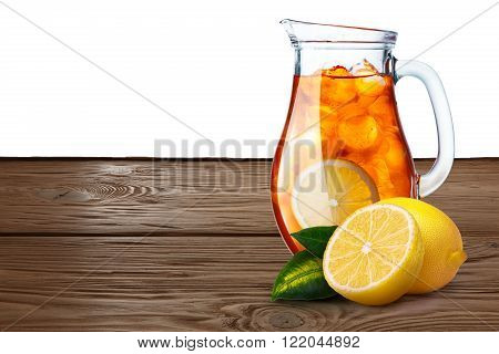 Jug Or Pitcher Of Iced Tea With Lemons On Foreground Standin On Wooden Table