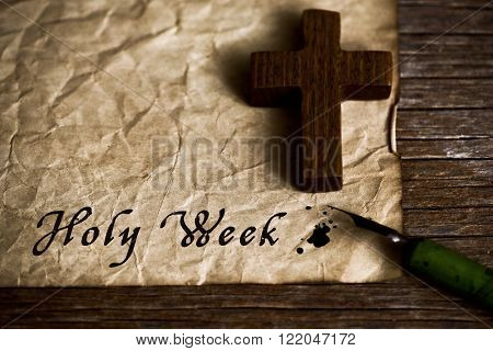 closeup of a small wooden christian cross, an old dip pen and a yellowish paper with the text holy week written with black ink in it, on a rustic wooden table