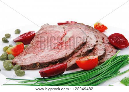 roasted meat served on white dish with capers