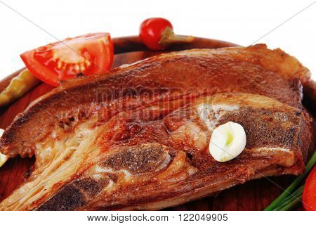 fresh hot roasted beef meat bone steak on red wooden plate with red hot pepper and capers isolated over white background