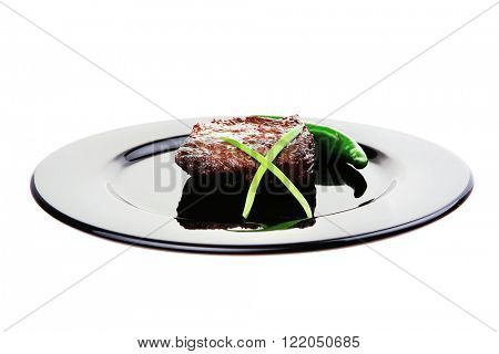 meat savory : grilled beef fillet mignon on black plate with pepper and chives isolated over white background