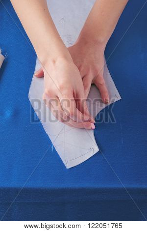 seamstress makes drawing on blue cloth in studio. Top view
