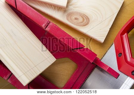 Cutting boards using the miter box and saw on the wooden background