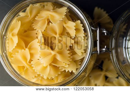 Many farfalle in a glass container for food storage close up black background