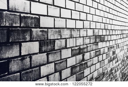 black brick wall with diminishing perspective closeup. black and white background