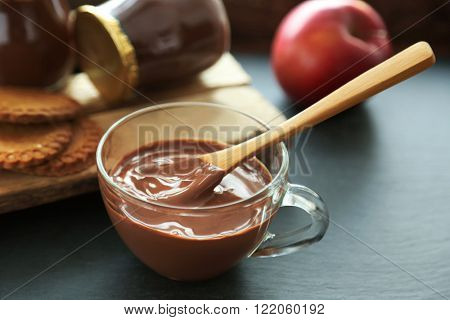 Melted chocolate in bowl, on wooden background
