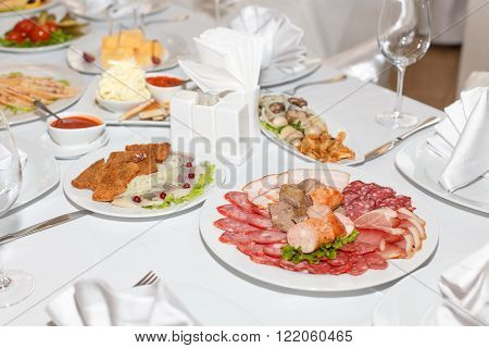 Sausages cold cuts dishes on a white banquet table in restaurant