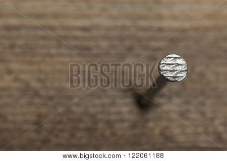 close up view of a nail into a wooden plank