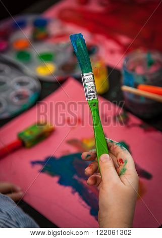 Child hand holding dirty brush used for painting pictures at home