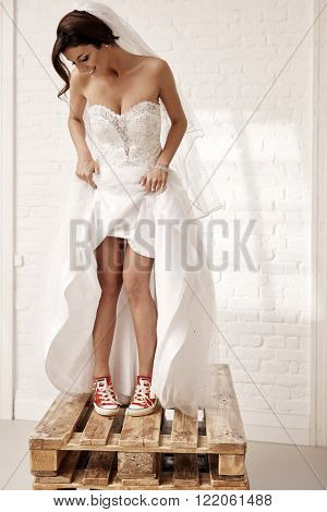 Cool bride standing on pallet in red sneakers and white wedding dress.