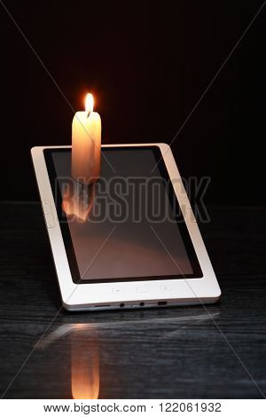 Blackout concept. Lighting candle on tablet screen against dark background