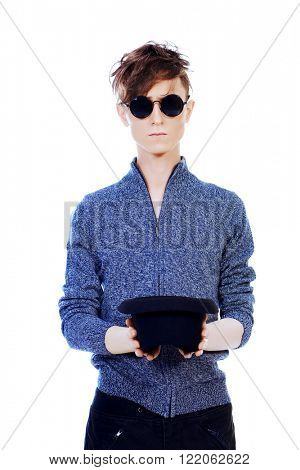 Strange young man in round sunglasses holding a hat in front of him. Hipster style. Isolated over white.