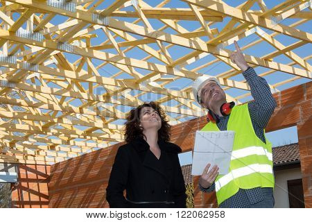 People Standing Over Unfinished Brick House With Wooden Roof Structure