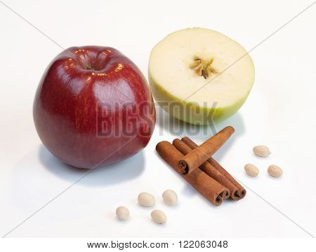 Red and green apple, cinnamon and peanuts on a white background