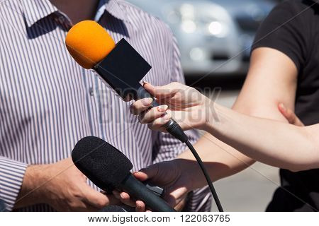 Journalists holding a microphone conducting TV or radio interview