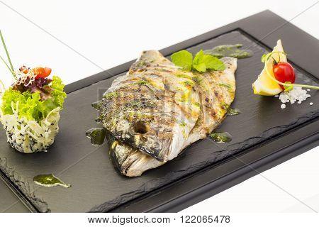 Fried fish dorado with vegetables and lemon